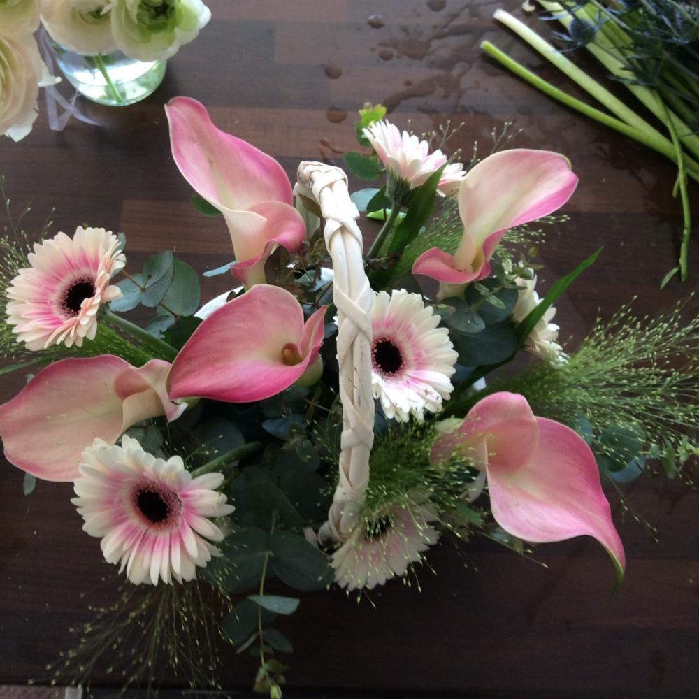 White basket, calla lilies, germini, foliage